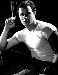Marlon Brando wears his iconic fitted, short-sleeve white t-shirt and poses with a lit cigarette.