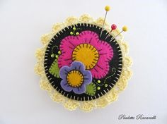 Felt pin cushion with embroidered flowers in black, pink, periwinkle