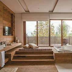 Já pensou chegar em casa e encontrar um banheiro assim? Êeeee, vida boa! A suíte do casal deste projeto tem uma verdadeira sala de banho com terraço, com madeira de demolição na parte seca do piso e nas paredes. Um painel apoia a TV, que é vista da banheira. Para relaxar, há ainda um futon. Projeto da arquiteta Lica Cukier. #arquitetura #banheiro #reforma #spa #terraço #vista #greatview