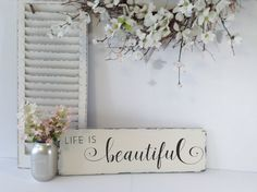 "Carve out your own inspired space with this rustic farmhouse wood sign from Wood Finds. Hand-tailored in minute detail, it features a pine wood base that is painted in ivory latex and features the phrase ""Life Is beautiful"" in a hand lettered scrolling text. It is a uniquely sophisticated home decor accent that will add a farmhouse chic to your existing decor. As a gift, it will make a lovely sentiment to share with your recipient. This is an original Wood Finds creation. Order now to…"