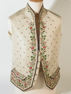 Mans waistcoat - Blue, black, brown, green, red, and pink embroidery in rose and shamrock design on background of cream silk. Dentate design in mauve and brown around borders. Strap and buckle at back. Lace frill sewn to edges probably added for theatrical purposes. Small stand up collar, straight waistcoat. 1780 (circa)