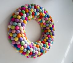 A fun and colourful felt ball wreath. Perfect for adding a touch of cheerful delight to your home or special event. This colourful felt ball wreath is handmade from felted wool balls in a rainbow of colours. Hang it on a door, window above a mante. Felt Ball Wreath, Pom Pom Wreath, Pom Poms, Bauble Wreath, Advent Wreath, Modern Holiday Decor, Modern Christmas, Green Christmas, Christmas Chair