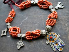 Africa |  Vintage necklace (brought in Morocco in the 1980s) that combines an enameled Hamsa, coral coloured glass, and a range of silver alloy beads and pendants.
