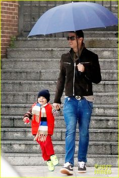 Cristiano Ronaldo holds onto his two-year-old son Cristiano Jr.'s hand as they head out on a rainy afternoon on March 6, 2013