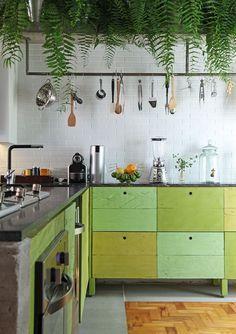 Nesta cozinha, de Paulo Castellotti, os armários foram produzidos com madeira de demolição pintada com spray – para não perder a textura do material em diversos tons de verde. De ares industriais, o ambiente tem parede com revestimento brancos estilo metrô e uma prateleira alta para samambaias.