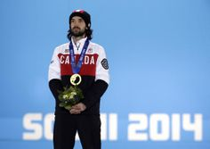 Charles Hamelin (Sainte-Julie, Quebec) of Canada, who won the gold medal in men's 1,500-meter short track speedskating stands on the podium during the medals ceremony at the 2014 Winter Olympics, Monday, Feb. 10, 2014, in Sochi, Russia. (AP Photo/Morry Gash)