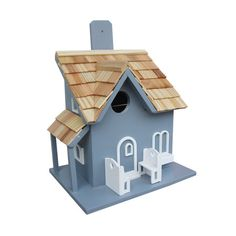 "BIRD HOUSE – Offer feathered friends a cozy abode with this beautifully crafted birdhouse, showcasing a pine-shingled roof and charming benches. Product: Birdhouse Construction Material: Exterior grade ply-board, kiln-dried hardwoods, polyresin and pine wood Color: Blue and natural Features: Removable back walls for easy cleaning Ventilation and drainage1.25"" Hole openings designed to accommodate common birds Dimensions: 8.125"" H x 7.875"" W x 5.875"" D"