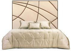 The distinctive hand carved patterning of this unique headboard adds an air of architectural artistry to a contemporary bedroom.