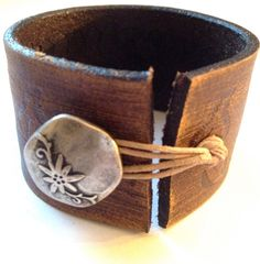 leather cuff. would be an idea for an old belt & decorative button... :D want!