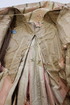 Inside view, robe à la francaise, France 1775-1799. Ivory and pink striped silk brocade with polychrome floral sprays, decorated with self fabric padded diamond bands, serpentine ovals and self fabric silk brocade bows edged in lace, linen lining.