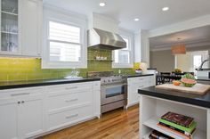 Like how kitchen connects to next room with crown molding. Kitchen is appealing with white cabinets, black countertops, large chartreuse subway tiles, and under counter lights.