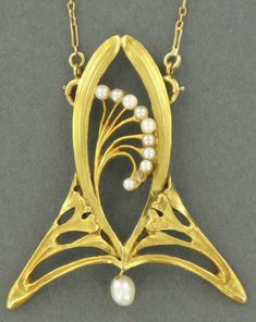 An Art Nouveau natural pearl and gold pendant. A finely carved brooch with stylised ginkgo leaf motifs, set with natural pearls, suspended from a fine gold chain.