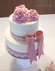 A white fondant covered chocolate cake with vanilla bean buttercream for a beautiful winter wedding. With sugar roses, a dusty pink fondant bow and piped lace detail.