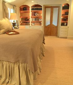 The Stone House master. Love the bedskirt, painted bookshelves, the doors, seagrass...