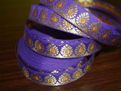Beautiful Egg Plant Color Floral hand-loom border from India, Jacquard ribbon border trim. Trim is decorated with golden metallic thread embroidery.   ➤ This listing is sold by (8 yard) Width:...