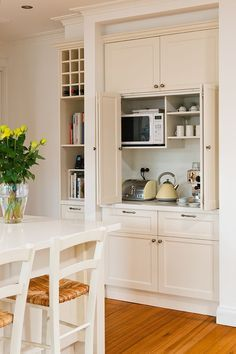 Microwave, toaster oven, coffee appliances all together and hidden behind doors. Love this!