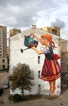 mural magnífica de una niña que riega un árbol, por Natalii Rak.  En Bialystok, Polonia