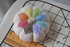 wool flowers on top of of a natural colored cotton linen pumpkin or tomato shape