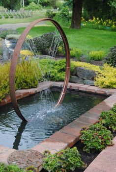 Wine barrel hoop and copper pipe water feature. I would use an old wagon wheel hoops that the wheels have rotted out of for sure.
