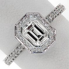 Emerald Bezel Elegante - The bright-cut bead-set diamond halo captivates a stunning 0.75 carat emerald cut center diamond in the Emerald Bezel Elegante. Divine lines with milgrain edges join the comfortable Euro shank fit and pedestal halo providing this ring with a stunning profile.