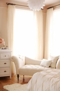 Warm light pours into this feminine, airy bedroom. Love the way the drapery accents the rest of the decor.
