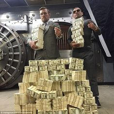 UFC fighter Conor McGregor (left) poses with training partner Artem Lobov and a stack of c...