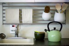 Ikea Grundtal shelf sideways from upper cabinets. Shelf becomes a towel bar, home for utensil caddies, hooks for hanging tools, etc. Just Genius!