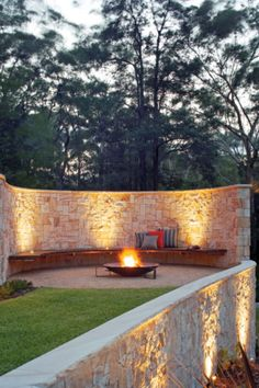 outdoor seating area.  wall, legless bench and fire pit.