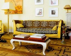Exotic and eclectic, the bright yellow leather sofa is grounded with global patterned cushions in neutral hues. A traditional patterned rug makes this eccentric seating seem commonplace. A golden color palette is primarily natural but incorporates a related burst of lemon yellow. Consistent and simple white framing around unique art allows the eye to appreciate the art and references the Asian inspired low and curvaceous coffee table. Minimal decoration allows the seating and purposeful…