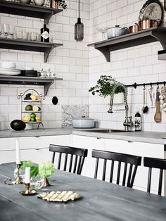 Dark grey shelving and concrete worktops, offset by sleek back chairs
