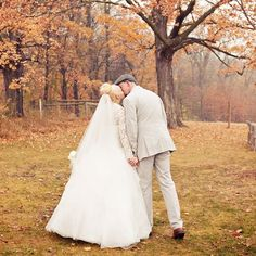 The newlyweds shared a kiss by a big tree showing the changes of fall in the atmosphere. The orange color of the leaves will remind the couple of the fall wedding they had. Photo Credit: Bellagala