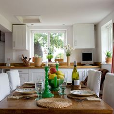 Kitchen-diner with white shaker-style cabinetry, wooden worktops, wood dining table and white chair covers