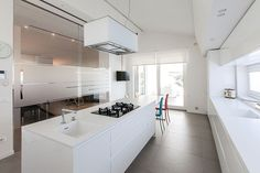 Spacious contemporary kitchen in white full of natural light
