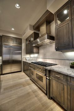 Located in Paradise Valley/Phoenix, Arizona, and built by Cullum Homes, this flawless kitchen boasts stainless steel Viking appliances, wood flooring, granite counter tops, and gray cabinetry.