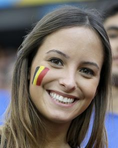 A Belgian fan shows off her national team's colors on her cheek before the group H World Cup soccer match between South Korea and Belgium at...