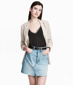 Light denim blue. Short, 5-pocket skirt in washed denim with distressed details. Darker sections at back. Button fly, slit at front, and raw-edge, frayed