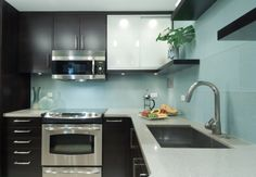 Large blue-ish glass tile slabs with black cabinets, white glass countertops