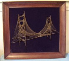 Fantastic framed string art of suspension bridge made out of wire and nails strung on black velvet in a good solid wood frame. Very very cool. Great