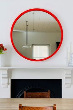 Hang a round mirror over your fireplace for an instant focal point. Vibrant red lacquer adds a pop of colour in this otherwise neutral scheme. #roundmirror #largeroundmirror #redmirror