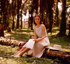 Audrey Hepburn writing a letter in a palm grove, 1955.