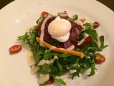 Biltong arugula salad served with oven dried tomatoes, julienned mango, poached quail egg and drizzled with a Cape vinaigrette Oven Dried Tomatoes, Beef Salad, Biltong, Quail Eggs, Arugula Salad, Tasting Menu, Grass Fed Beef, Vinaigrette, Cape