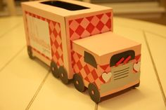 -large kleenex box and a smaller square gift box  -white craft foam for head lights  -metallic black (1 - 12x12 piece) cardstock  -baby pink bassil cardstock (3 - 12x12 pieces)  -argyle scrapbook paper (1 - 12x12 piece)  -10 pink brads  -cardboard for wheels  -red craft foam for windshield wipers  -gray scrap paper for grill  -white cardstock  -pink alphabet stickers