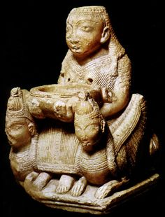 The Canaanite goddess is shown seated between winged cherubim with lion's bodies and women's heads. Phoenicians brought this deity to southwestern Iberia.  She is an alabaster ritual vessel; when libation is poured into her,  the liquid shoots out from her breasts into the basin she holds.