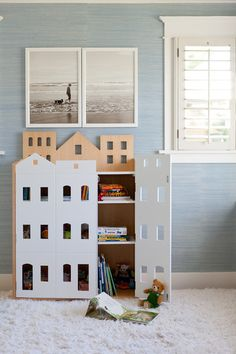 14. A home for books. A bookcase with house-like doors hides clutter and can even stand in as a mod dollhouse. Craft your own take on this by painting (trace first) simple window, door and roof shapes on the outside of a plain cabinet.