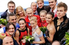 Russian President Vladimir Putin, centre back, poses for a photograph with the Russian team after they placed first in the team figure skating competition. (David J. Phillip/AP)