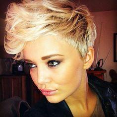 Pour un effet très tendance, les cheveux de cette jeune femme sont courts sur les côtés et à l'arrière, mais beaucoup plus longs sur le dessus de la tête. Le coiffeur a ensuite ramené ces cheveux vers l'avant, en les relevant, et a tourné les pointes. La coloration blonde aux racines foncées ajoute du caractère à la coiffure.