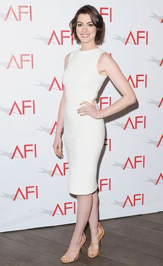 Anne Hathaway wearing a white body con sleeveless dress and ankle strap heels