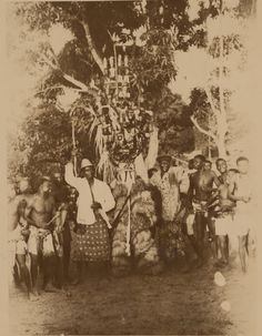 Nigeria, Ibo adult male [?] wearing masquerade costume surrounded by large group of male adults and children. Photographed by Edward Rowland Chadwick, ca 1927-1943