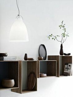 design insolite d'étagère en bois foncé, lampe de lecture a poser blanche, plante verte