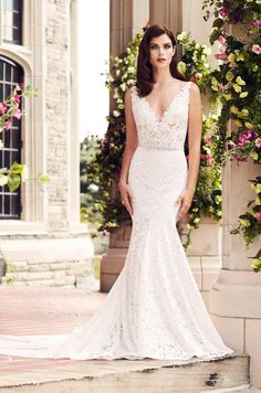 Lace fit and flare gown with v-neckline on bodice lined in nude tulle, lace appliques around the neckline, and a beaded belt at the waist.